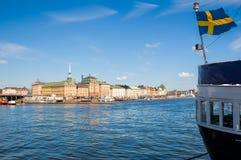 与挥动瑞典旗子的斯德哥尔摩都市风景 免版税库存图片
