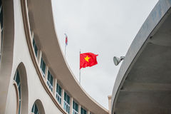 与挥动的横幅的金属杆 红旗黄色星,在两个圆的房子之间 起波纹的纹理 越南的国民 普遍 库存照片