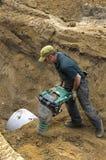 与振动片堵塞器的工作者变紧密的沙子 免版税图库摄影