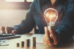 与挽救金钱的企业accountin用拿着电灯泡的手 免版税库存照片
