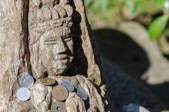与捐赠的硬币的木菩萨雕塑在镰仓 免版税库存照片