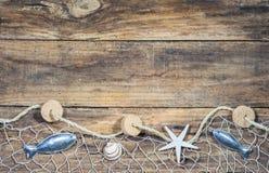 与捕鱼网的海船舶装饰在棕色木头 库存图片