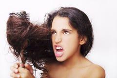 与掠过她难驾驭的头发的女孩画象的护发概念 库存照片