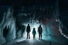 与探索神奇冰洞穴洞的人的超现实的风景 室外的冒险 探索巨大的冰冷的洞的家庭 免版税库存照片