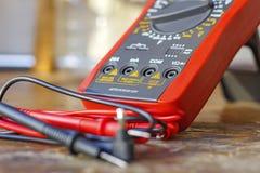 与探针的数字式多用电表在一张木桌上在车间 免版税库存图片
