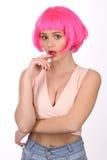 与接触她的嘴唇的桃红色头发的模型 关闭 奶油被装载的饼干 库存照片
