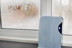 与接触控制板工作的抽湿机在舱内甲板的湿窗口旁边 在窗口写的湿气 潮阴阴概念 免版税库存图片
