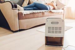 与接触控制板,湿度指示剂,紫外灯,空气ionizer,水在公寓的容器工作的抽湿机 关闭 免版税图库摄影