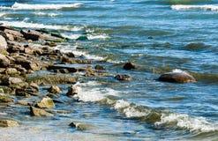 与接踵而来的波浪的岩石岸 图库摄影
