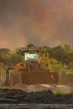 与接近的林区大火背景的前端装载机  图库摄影