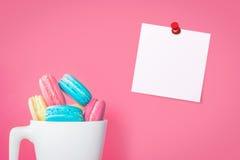 与推挤别针的空的纸笔记板料用在桃红色背景的蛋白杏仁饼干 免版税图库摄影