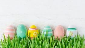与掩藏在绿色gra的五颜六色的鸡蛋行的复活节背景  免版税库存图片