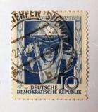 与描述在世界的地球的后一个人的图象的老蓝色东德邮票团结 库存照片