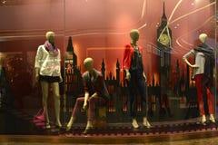 与提包的母时装模特在时尚商店窗口里在假日 库存图片