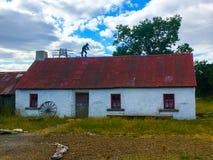 与提琴手的土气老被粉刷的爱尔兰村庄屋顶的 免版税图库摄影