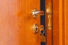 与插入键的门在对此的匙孔和房子象 免版税库存照片