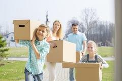 与搬入新房的纸板箱的家庭 免版税库存图片