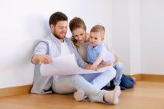 与搬到新的家的图纸的愉快的家庭 免版税库存照片