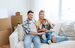 与搬到新的家的箱子的愉快的家庭 免版税库存照片