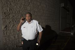 与携带无线电话和火炬的治安警卫在晚上巡逻 免版税库存照片