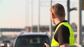 与携带无线电话的交通警工作在高速公路 股票视频