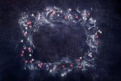 与搽粉的糖和冰糖心脏装饰框架的黑石背景  恋人的礼物在华伦泰` s天 概念亲吻妇女的爱人 免版税图库摄影