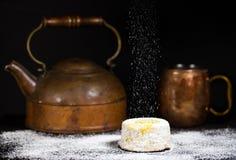与搽粉的糖毛毛雨的柠檬蛋糕在与古色古香的铜茶罐和杯子的黑暗的背景 库存照片