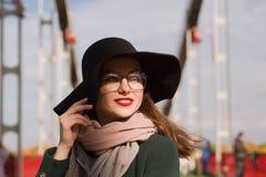与摆在城市的明亮的构成的愉快的年轻模型 妇女w 免版税库存照片
