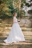 与摆在她的婚礼之日的新娘花束的美丽的新娘妇女画象 免版税库存照片