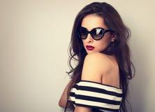 与摆在时尚sungl的长的头发的典雅的别致的女性模型 免版税库存图片