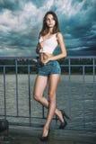 与摆在河附近的长的腿的时装模特儿 库存图片