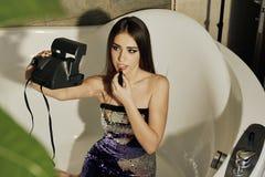 与摆在浴的长的深色的头发的年轻女性模型,绘有唇膏的嘴唇和在偏振光相机的做selfie 库存照片