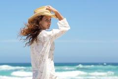 与摆在海滩的夏天礼服和帽子的时装模特儿 图库摄影