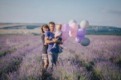 与摆在淡紫色领域的五颜六色的气球的愉快的家庭 库存图片