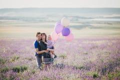 与摆在淡紫色领域的五颜六色的气球的愉快的家庭 库存照片