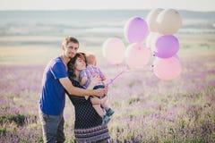 与摆在淡紫色领域的五颜六色的气球的愉快的家庭 免版税库存照片