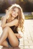 与摆在s光芒的长的金发的有吸引力的年轻模型  免版税库存照片