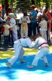 与摔跤手,和服的两个男孩战斗 免版税库存图片