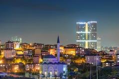 与摩天大楼和清真寺的夜场面 库存图片
