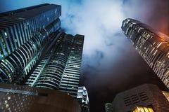 与摩天大楼的夜地平线在多云天空下 免版税库存图片