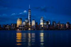 与摩天大楼的纽约曼哈顿街市地平线被照亮在哈得逊河全景 图库摄影