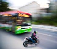 与摩托车骑士和公共汽车i的危险城市交通情况 库存照片