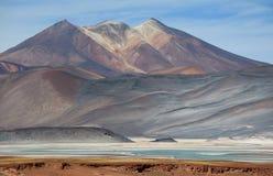 与撒拉族de Talar盐湖前景的,阿塔卡马沙漠,智利的美丽如画的塞罗Medano山 图库摄影