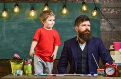 与支持他的父亲的滑稽的面孔的孩子 看在一个方向的爸爸和儿子 斜眼看象的聪明的衣服的人 免版税库存图片