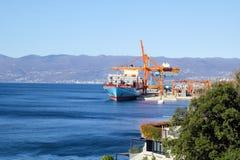 与支持的容器的集装箱船在口岸在天际/货物卸载过程的运输由海和物品的船口岸 库存照片