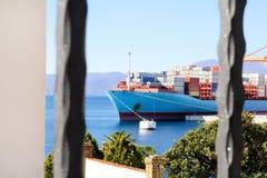 与支持的容器的集装箱船在口岸在天际/货物卸载过程的运输由海和物品的船口岸 图库摄影