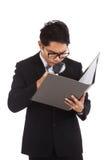 与放大镜检查数据的亚洲商人在文件夹 免版税库存照片