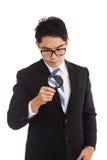 与放大镜的亚洲商人 免版税图库摄影