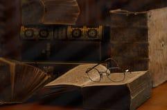 与放大镜的古色古香的书在一间多灰尘的屋子 免版税库存图片