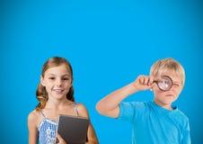 与放大镜的孩子在蓝色背景前面 库存图片